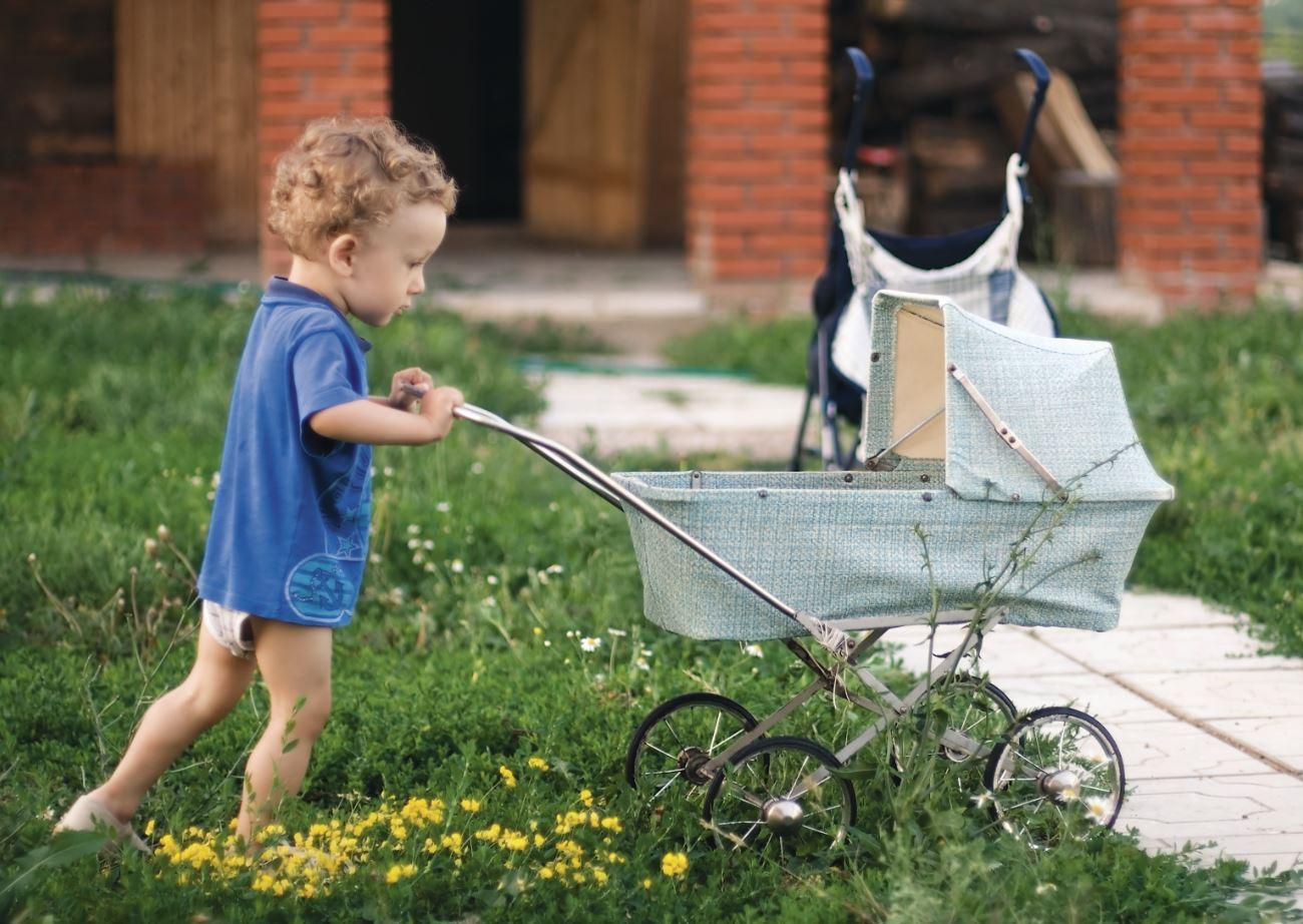 junge schiebt Puppenwagen