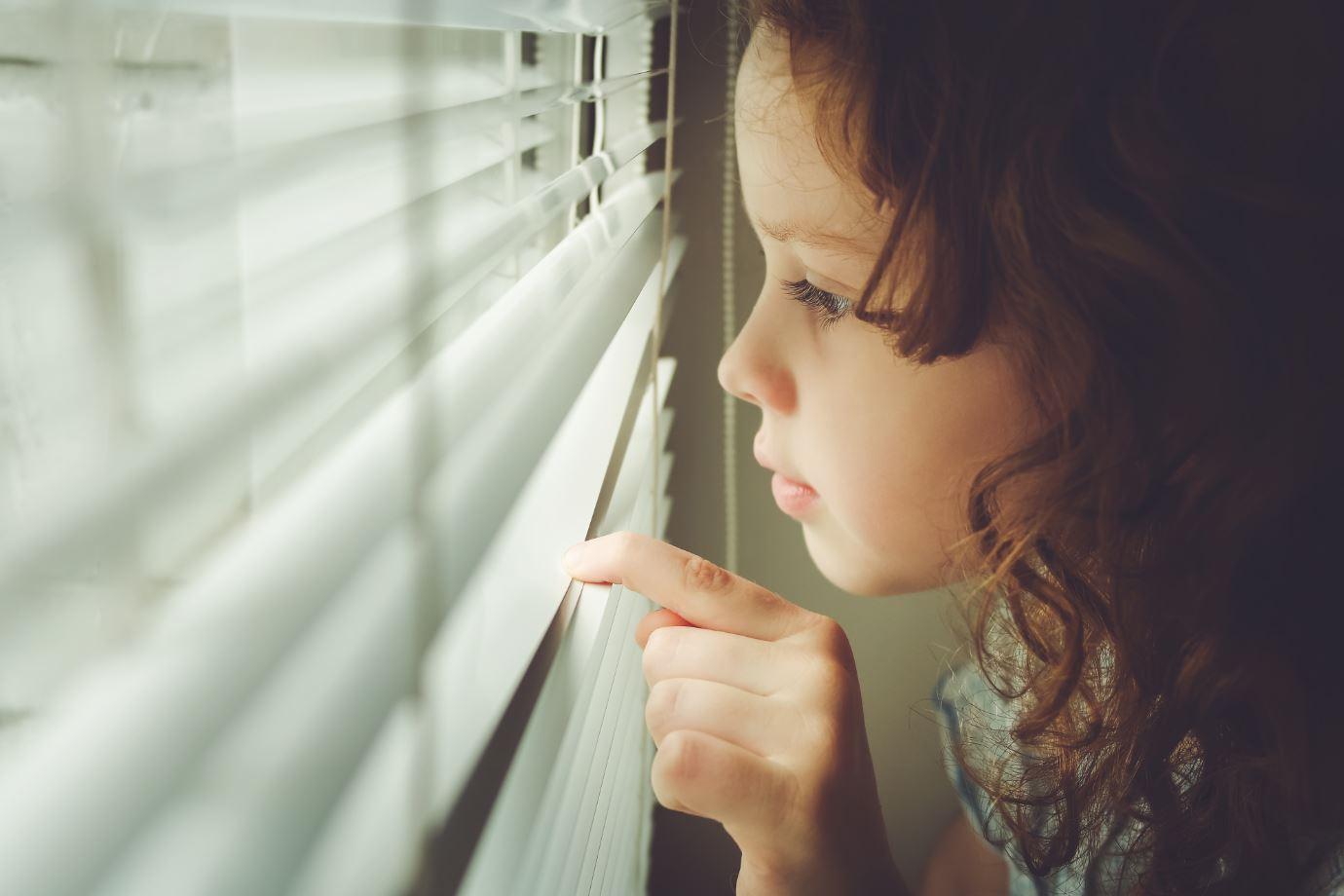 kind guckt aus Fenster