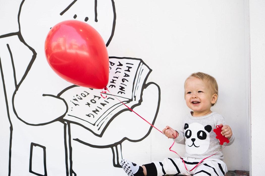 Kleinkind mit rotem Luftballon