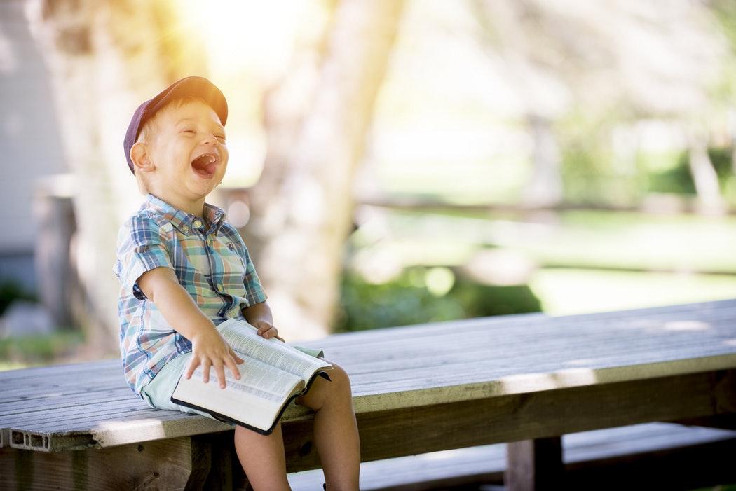 Junge liest Buch und lacht