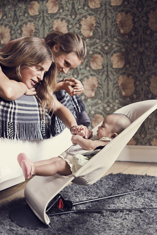 Frauen schauen auf ein Baby in der Wippe