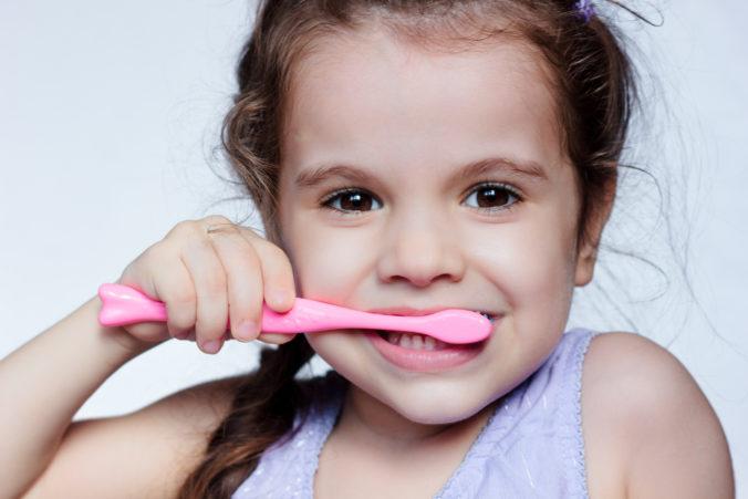 Kleines Mädchen putzt Zähne mit rosa Zahnbürste