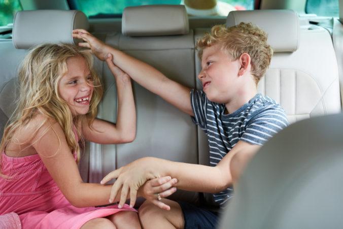 Zwei Kinder raufen und streiten im Auto