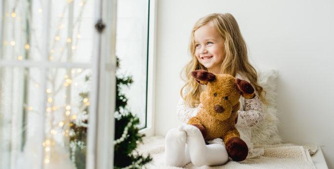 Kleines Mädchen mit Teddybär im Arm