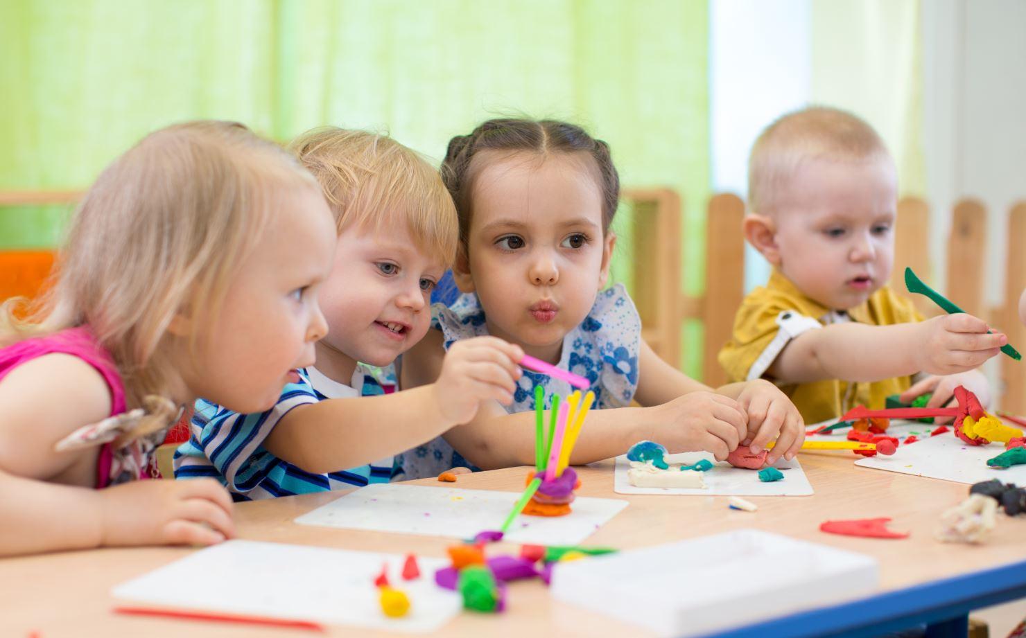 Kinder sitzen zusammen und malen