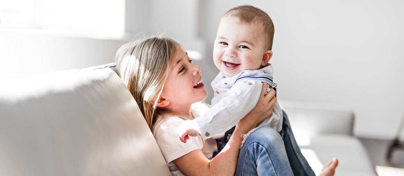 Kleines Mädchen mit Baby auf dem Schoß