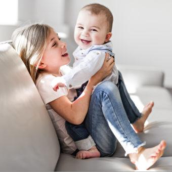 Kleines Mädchen mit Kind auf dem Schoß