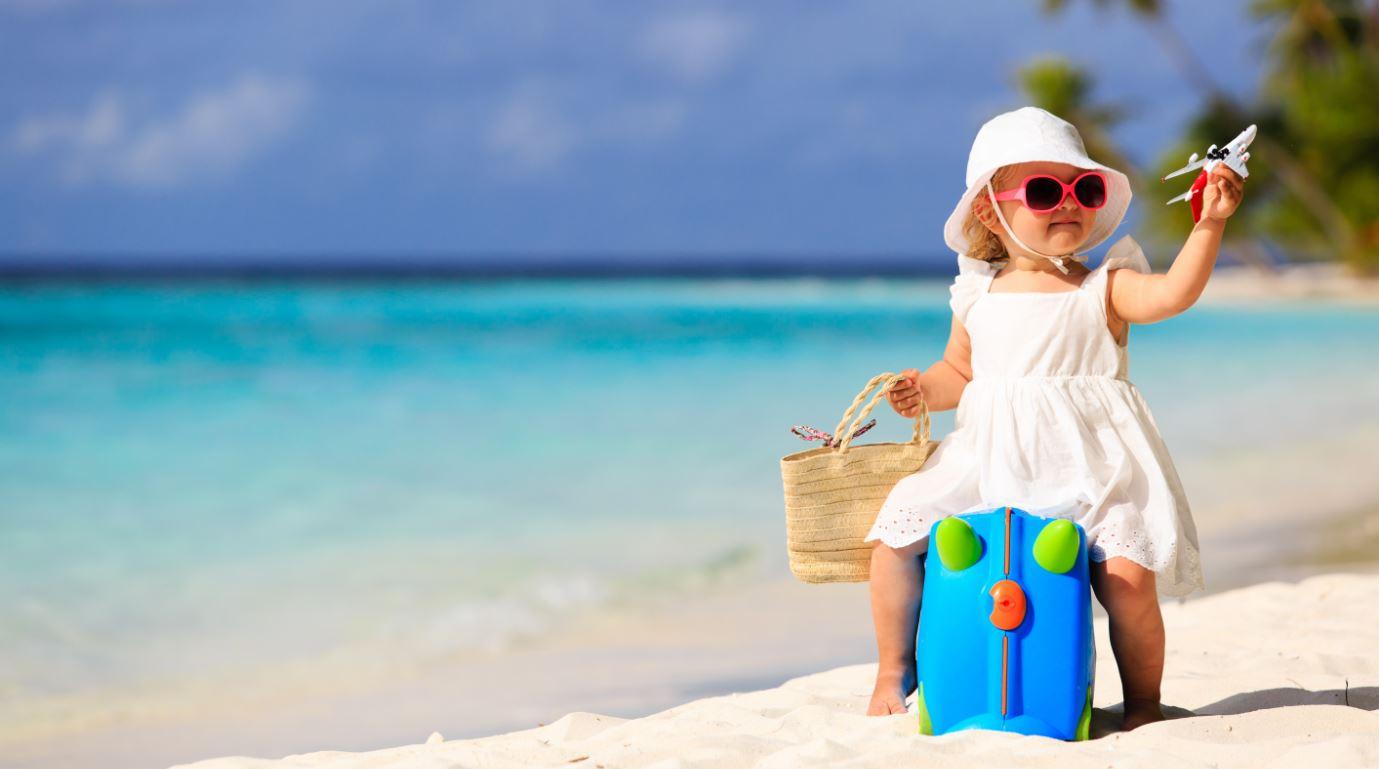 Kind mit Koffer am Strand