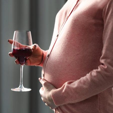 Schwangere Frau hält Weinglas