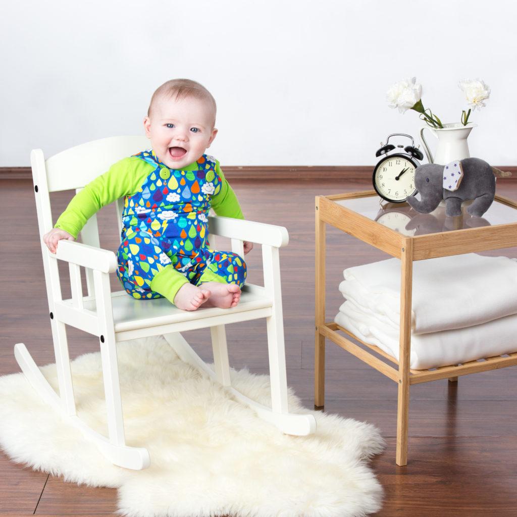 Baby mit Babauba bekleidet im Schaukelstuhl