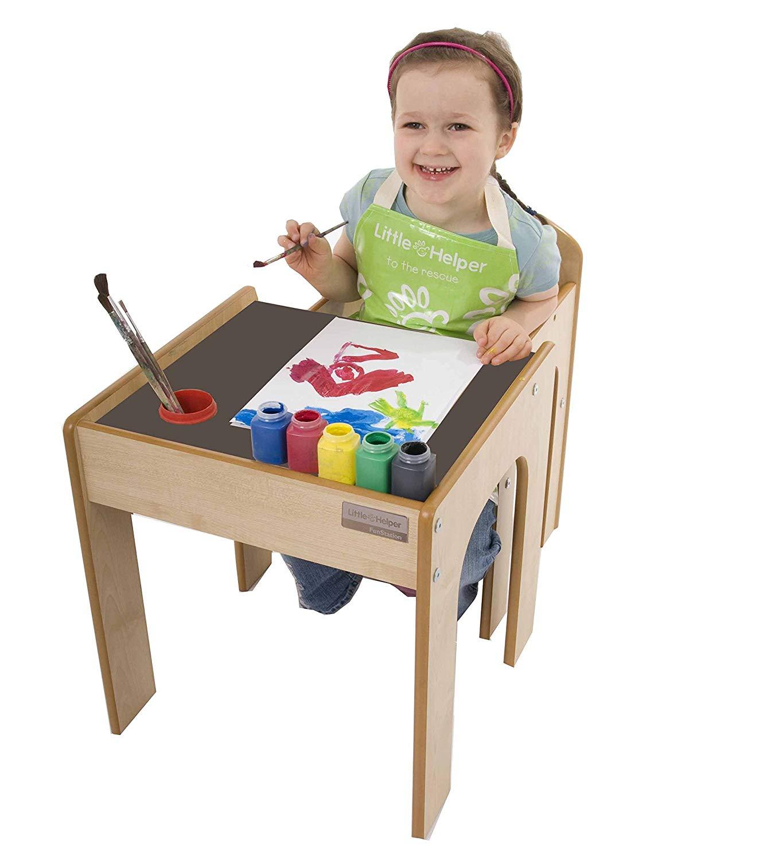 Kind sitzt am kleinen Tisch