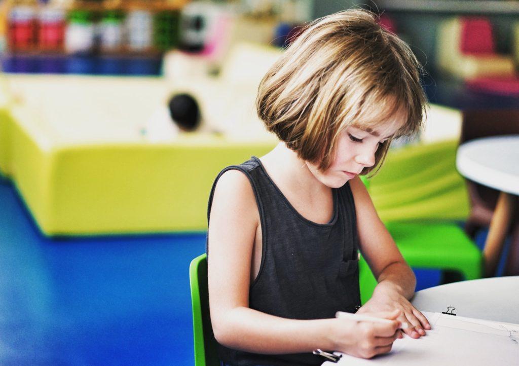 Kind malt allein am Tisch