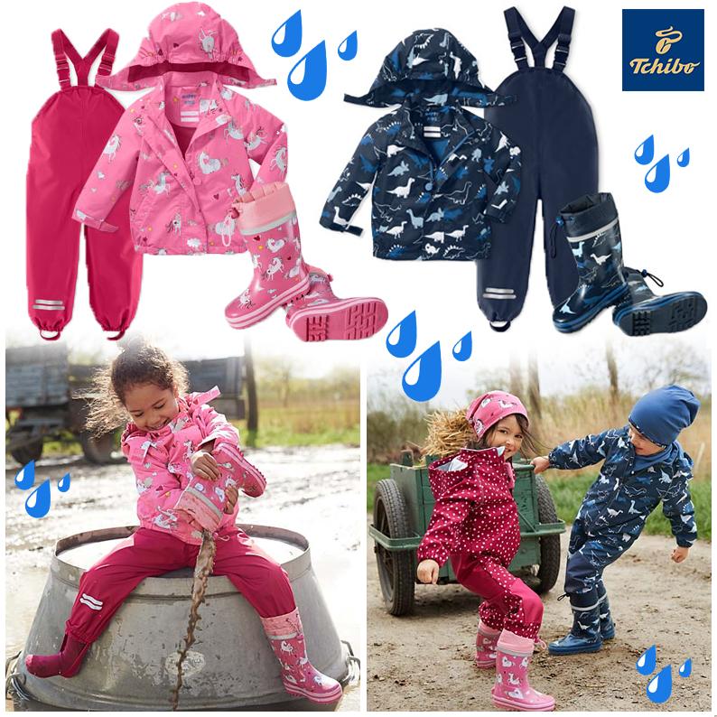 Mädchen und Junge spielen in Regenkleidung