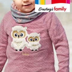 Kind trägt rosa Shirt mit Eulenmotiv
