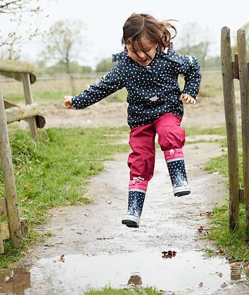 Mädchen springt mit Gummistiefel in Pfütze