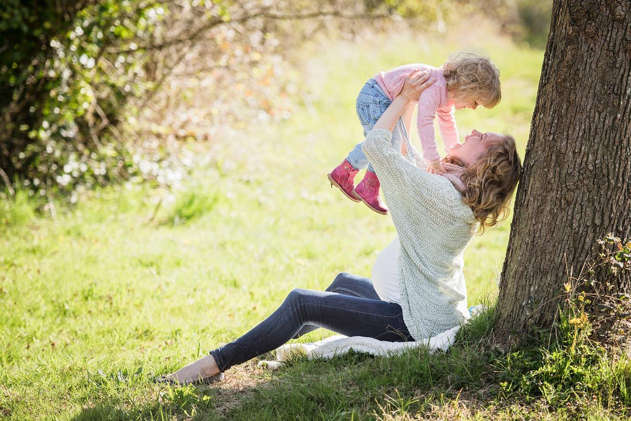 Mutter spielt mit ihrem Kind draußen im Park