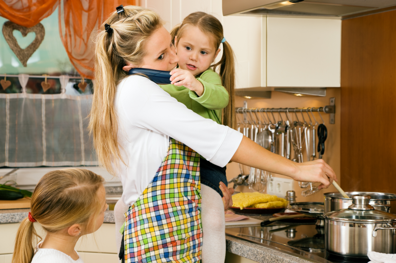 Mama kocht mit Kind auf dem Arm