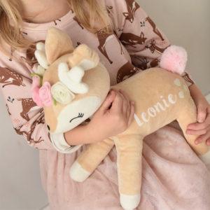 Kind hält Kuscheltier-Reh im Arm