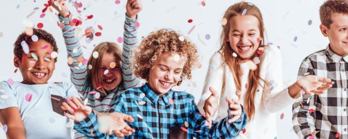 Kinder werfen Konfetti und lachen