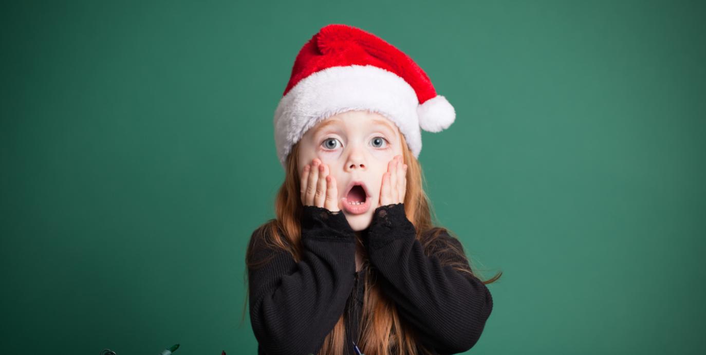 kind mit weihnachtsmütze guckt erstaunt