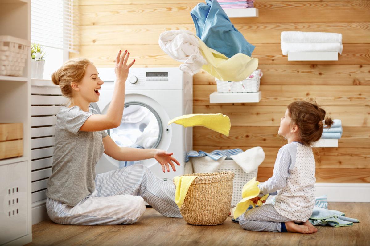 Mutter und Tochter spielen beim Wäsche-machen