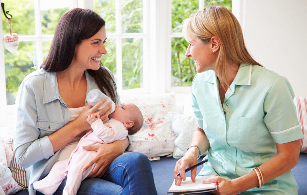 Hebamme berät Mutter nach der Geburt