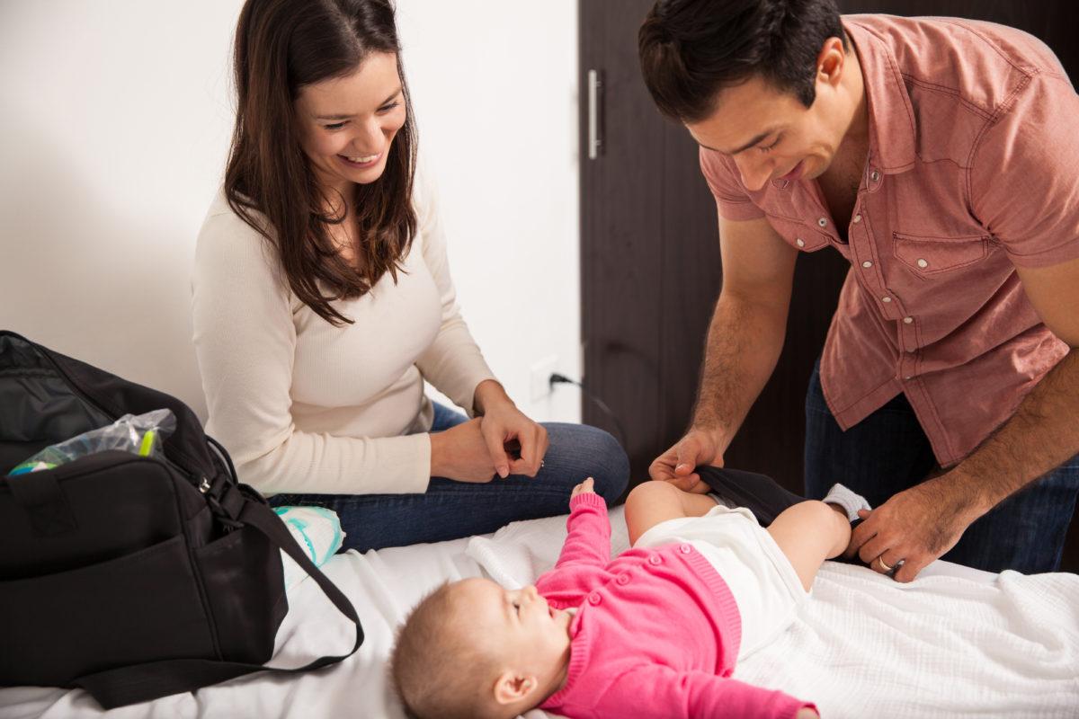 Eltern wickeln gemeinsam Baby