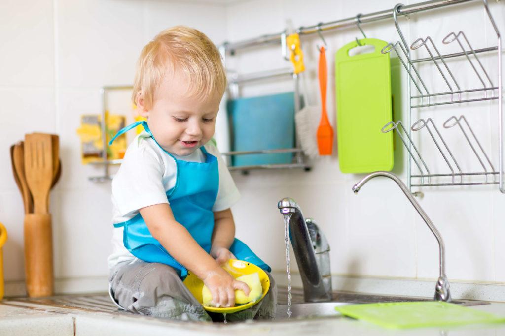 Kleinkind hilft beim Abwasch