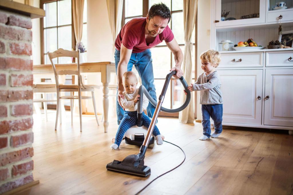 Papa saugt mit seinen Kindern die Wohnung