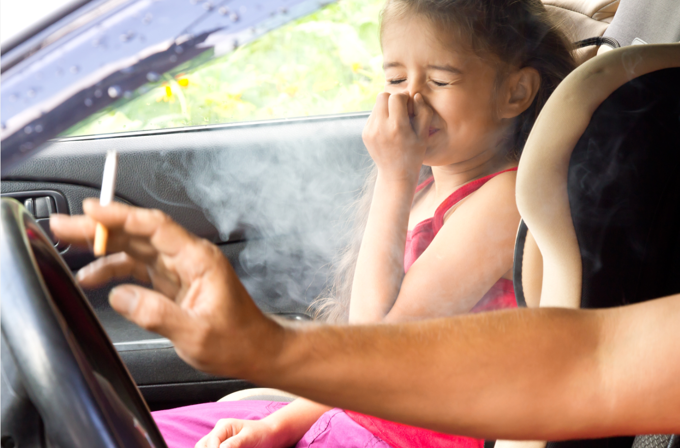 Mann raucht im Auto während das Kind auf dem Beifahrersitz sitzt
