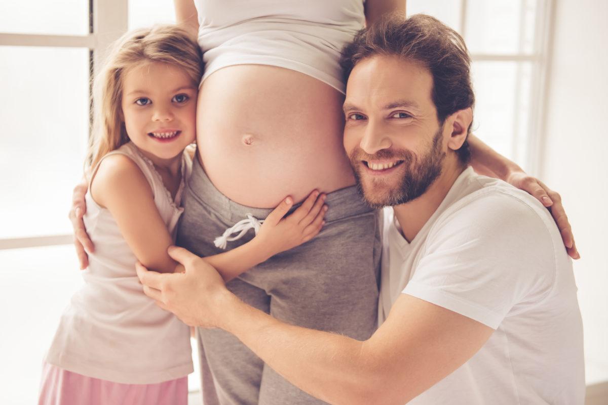 Vater und große Schwester an Babybauch