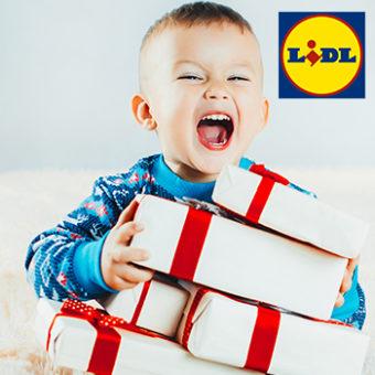 Kind sitzt lachend vor Geschenken