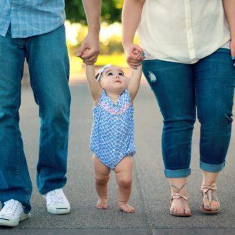 Eltern laufen mit einem Kind Hand in Hand