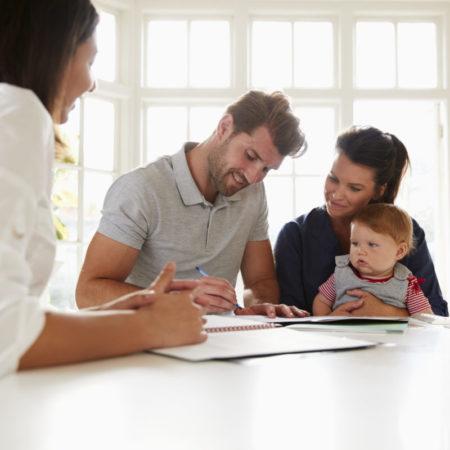 Familie mit Baby informiert sich über wichtige Versicherungen