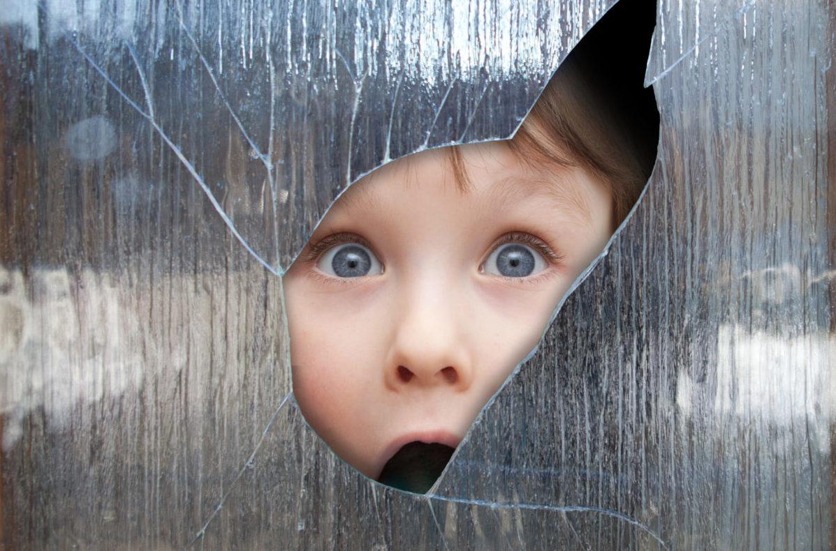 Kind guckt durch zerbrochene Scheibe
