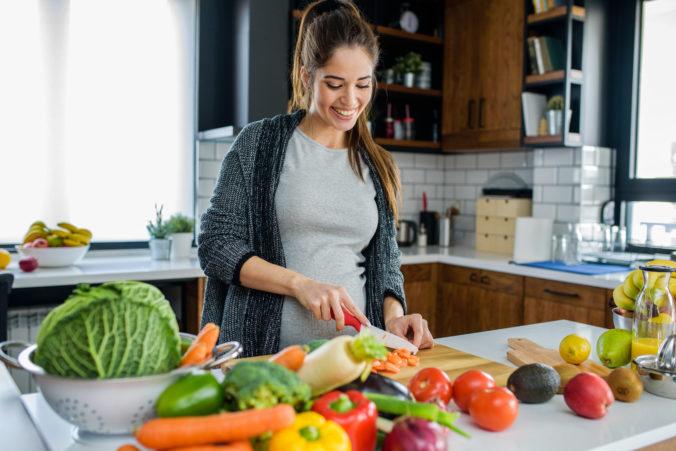 Schwangere schneidet Gemüse in der Küche