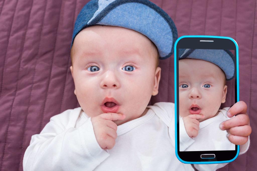 Baby hält Handy mit Foto