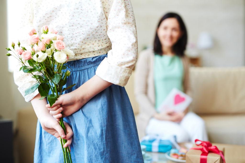 Mädchen hält Blumen für ihre Mutter hinter dem Rücken