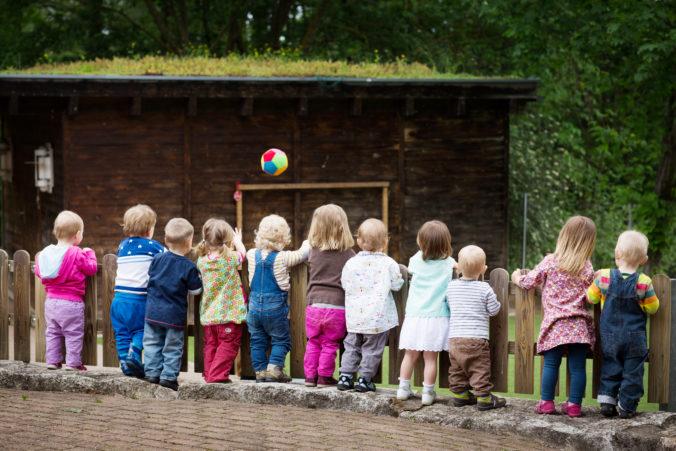 Kinder stehen am Zaun