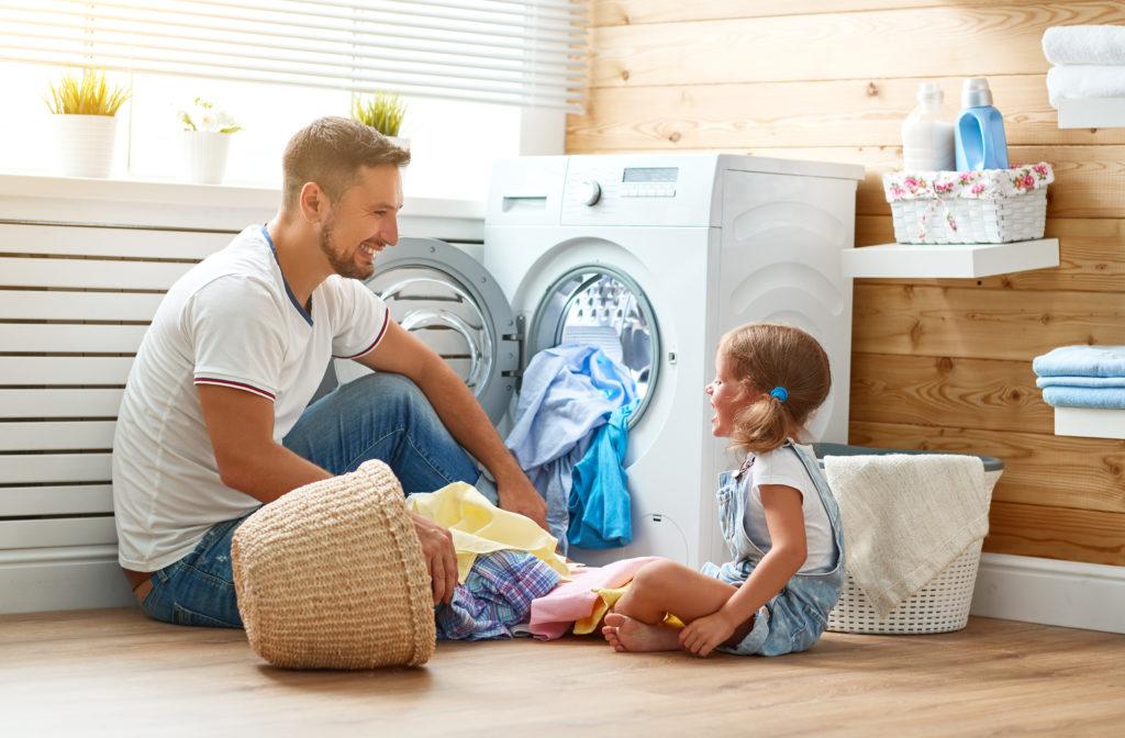 Mann sitzt mit Tochter vor der Waschmaschine