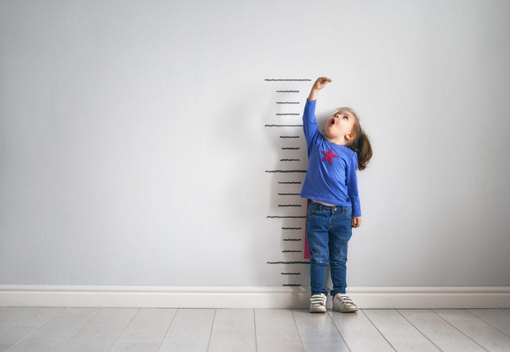 Kind steht vor Wand