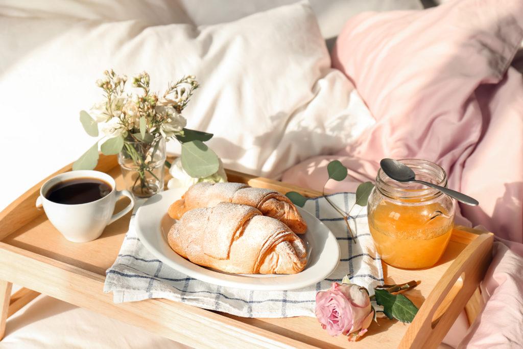 Frühstückstablett mit Croissants, Kaffee, Saft und Blumen auf dem Bett
