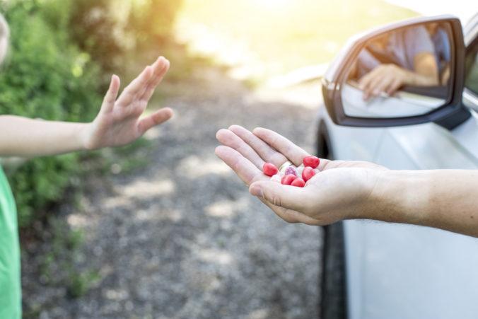Fremder Mann bietet Kind Süßigkeiten aus dem Auto heraus an