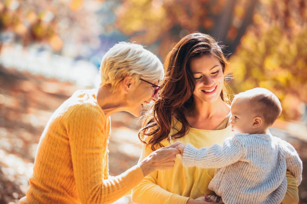 Mutter, Oma und Kind im herbstlichen Wald