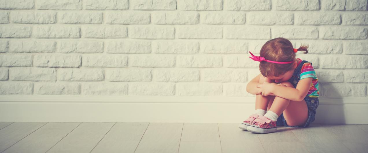 Kind sitzt traurig vor Wand