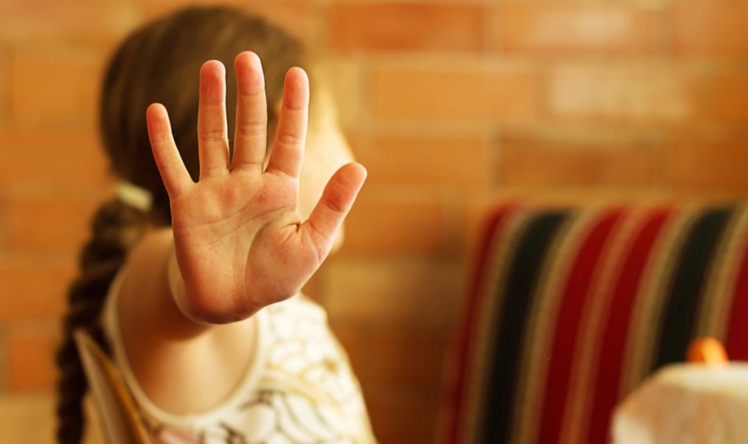 Kind streckt Hand als Stoppzeichen aus