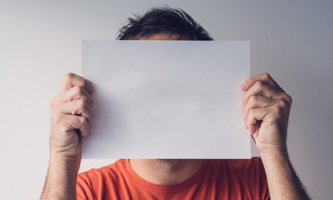 Mann versteckt Gesicht hinter Blatt