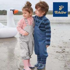 Mädchen und Junge tragen Regenhosen