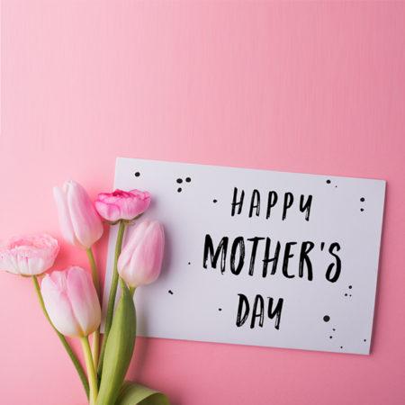 """Pinke Tulpen und Karte mit der Aufschrift """"Happy Mothers Day"""""""
