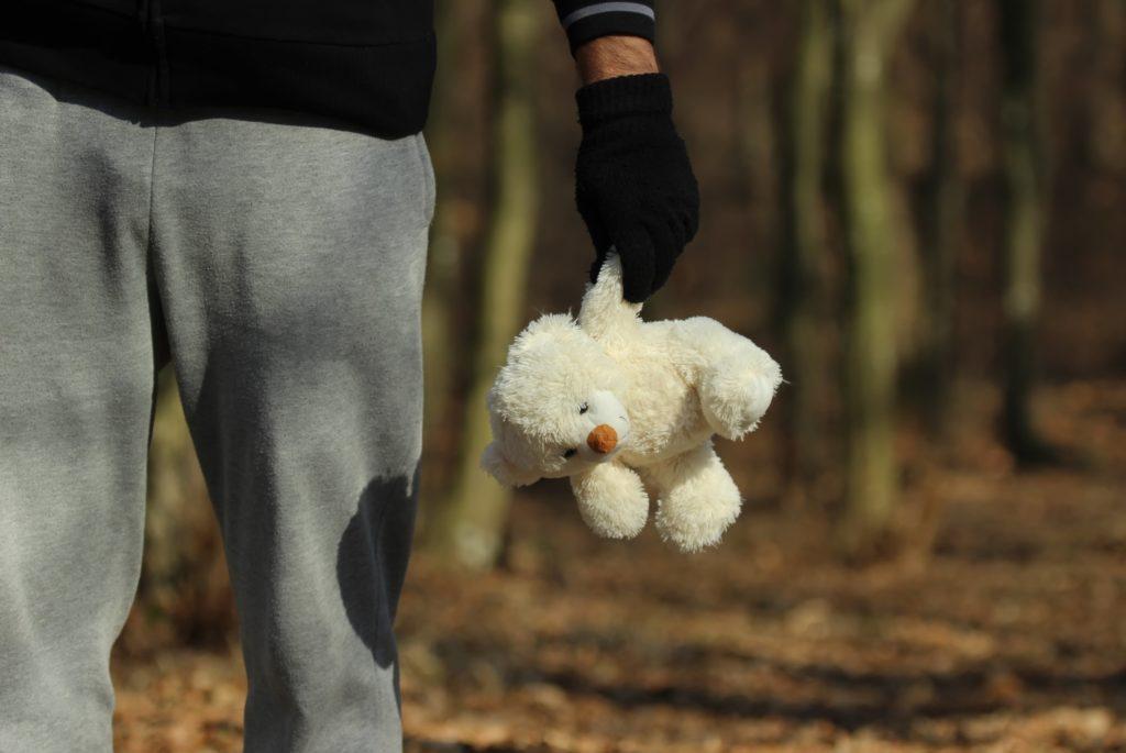 Mann im Wald mit Teddy in der Hand